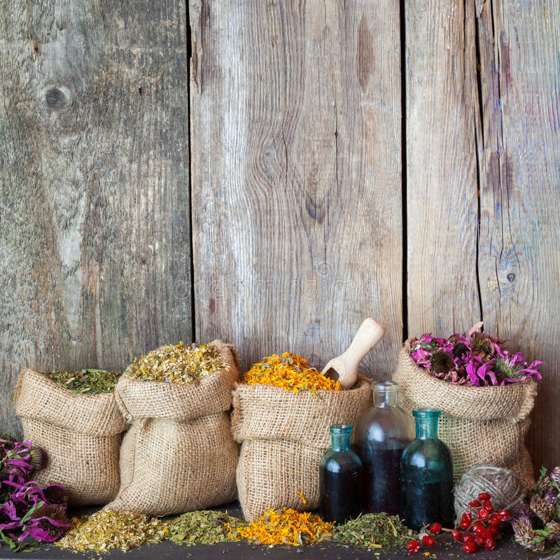 Healing herbs in hessian bags and bottles with tincture on. Healing herbs in hessian bags and blue bottles with tincture on old wooden background, herbal royalty free stock image