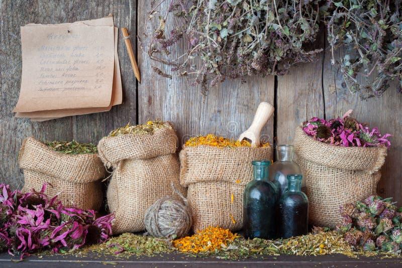 Healing herbs in hessian bags, herbal medicine. Healing herbs in hessian bags near wooden wall, herbal medicine stock image