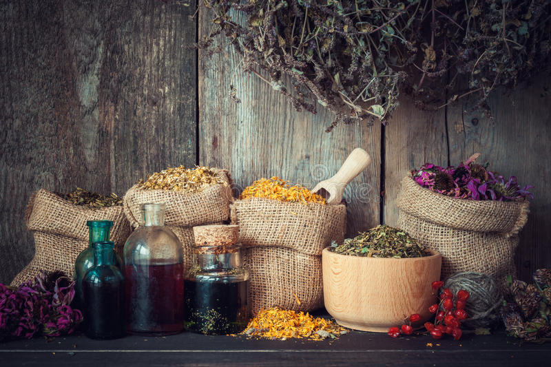 Healing herbs in hessian bags. Mortar and bottles of tincture or oil, herbal medicine royalty free stock image