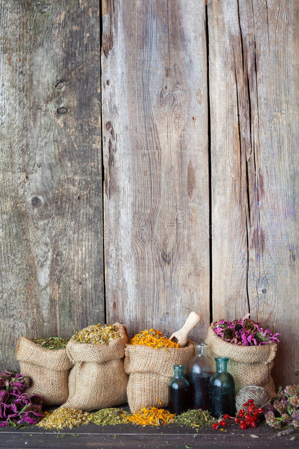 Healing herbs in hessian bags on old wooden background. Herbal medicine stock photos