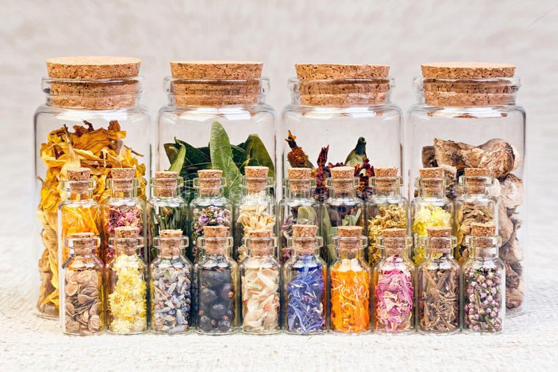 Healing herbs and tinctures in bottles on sackcloth, dried flowe stock photos