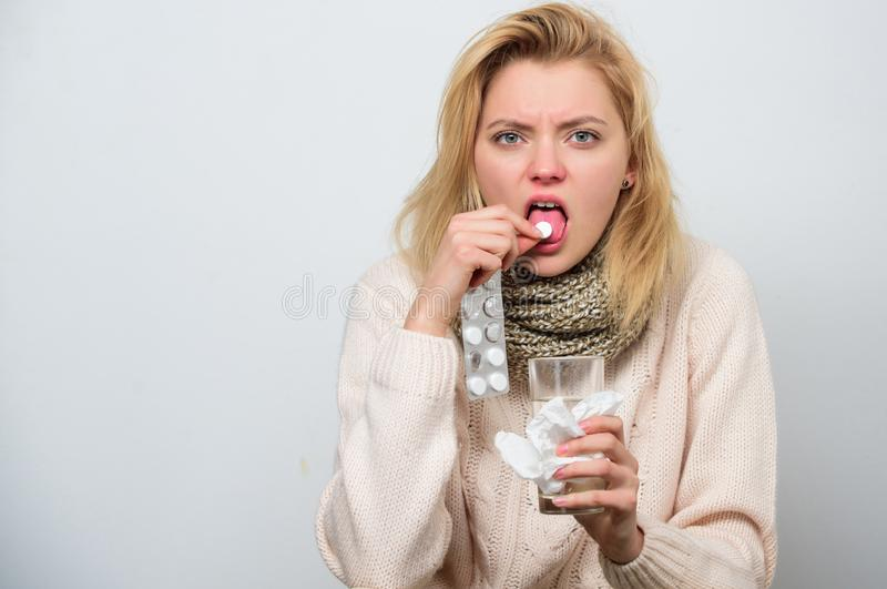 Healing pill. Cute sick girl taking anti cold pill. Ill woman treating symptoms caused by cold or flu. Unhealthy woman. Holding pills and water glass royalty free stock photography