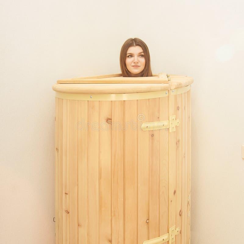 Healing spa treatment in cedar barrel. Young beautiful girl do salon procedure. Health accessories royalty free stock image