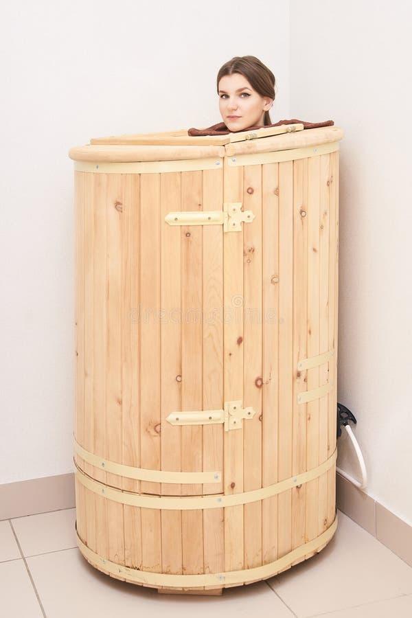 Healing spa treatment in cedar barrel. Young beautiful girl do salon procedure. Health accessories stock image