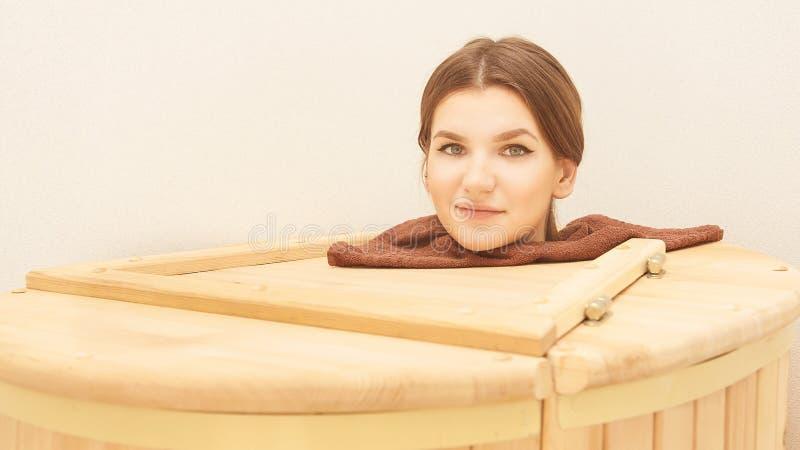 Healing spa treatment in cedar barrel. Young beautiful girl do salon procedure. Health accessories stock photo