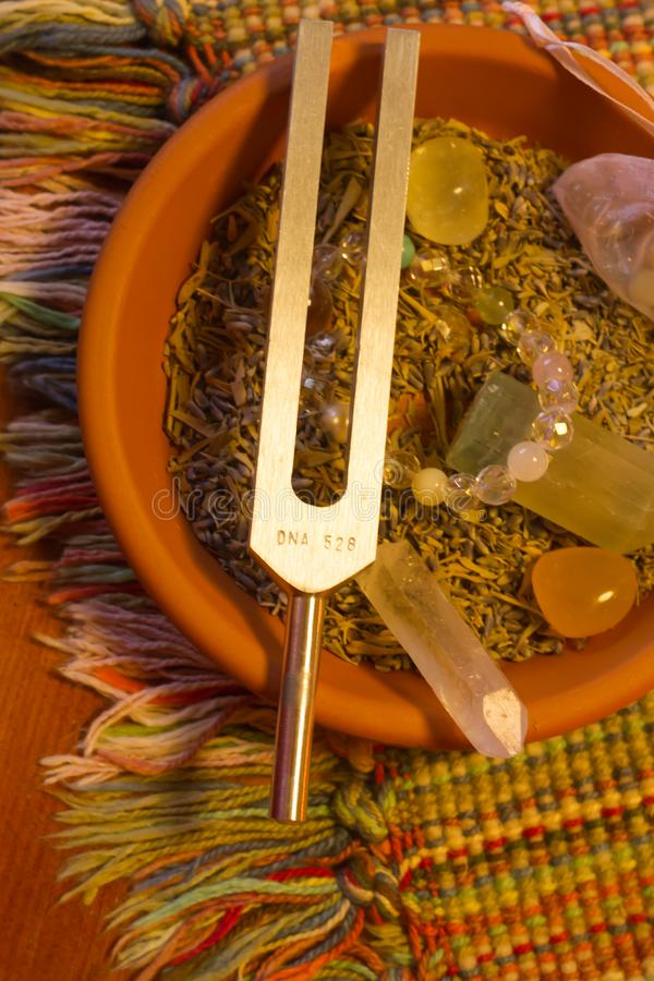 Healing tuning fork and crystal stone on table . stock images