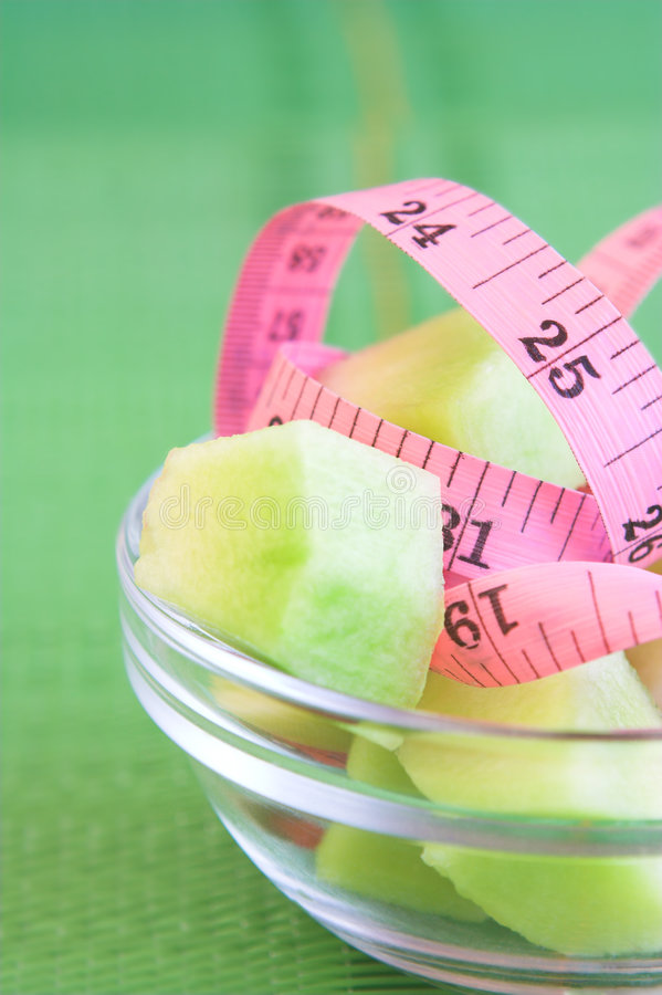 Health #1. Measuring tape and fruit in a glass bowl against a green background. Shallow D.O.F ? some of the measuring tape, fruit and bowl in focus ? background royalty free stock photos