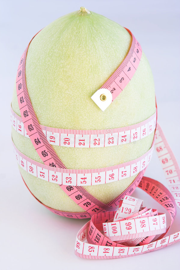 Health #5. Measuring tapes around a melon against a light blue background. Shallow D.O.F royalty free stock photography