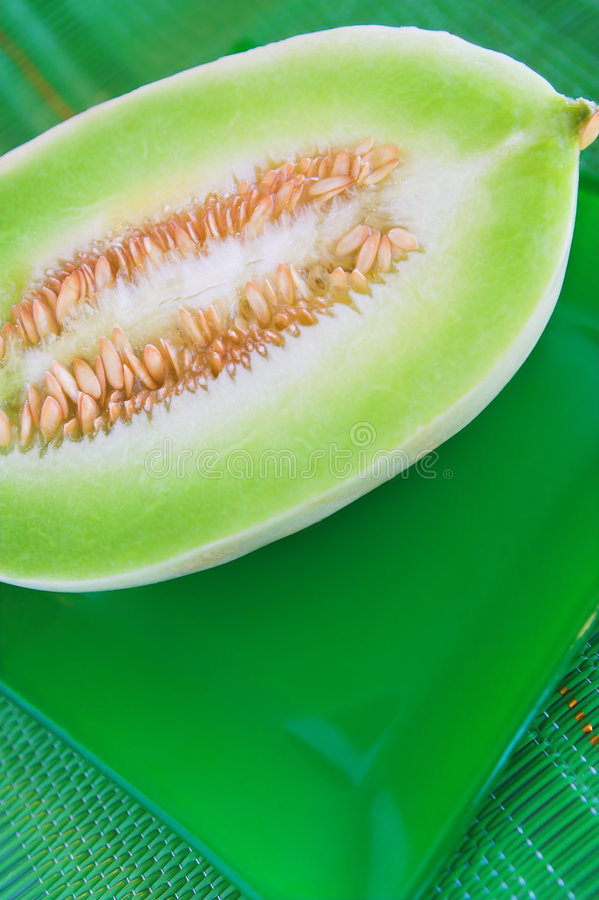 Health #7. A melon cut in half on a green plate and placemat stock image