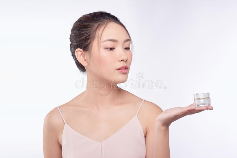 Health and beauty concept - Attractive asian woman applying cream on her skin.  royalty free stock images