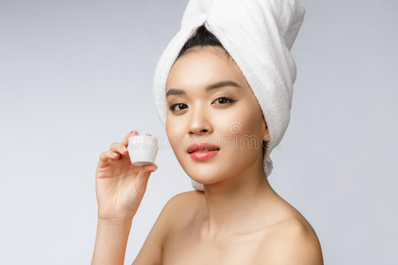 Health and beauty concept - Attractive asian woman applying cream on her skin, isolated on white. stock photography