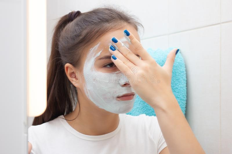 Facial skin care. Young girl makes a moisturizing cleansing face mask stock photography