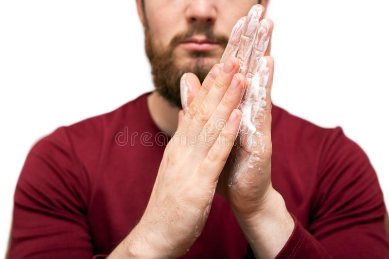 Health beauty and skin care concept. Closeup young bearded man with beard soap or shampoo on his hand for washing beard royalty free stock images