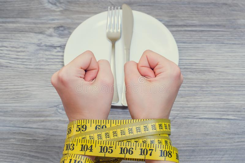 Health body care unhealthy eating dieting starving weight loss slimming. Concept of bad food habbits and unhealthy eating. Woman`. S hands royalty free stock image