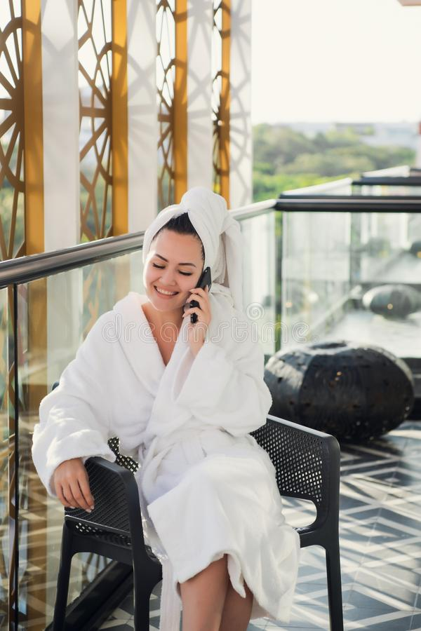 Health and body treatment. Portrait of young smiling woman in white bathrobe sitting on chair at cosmetic center on stock images