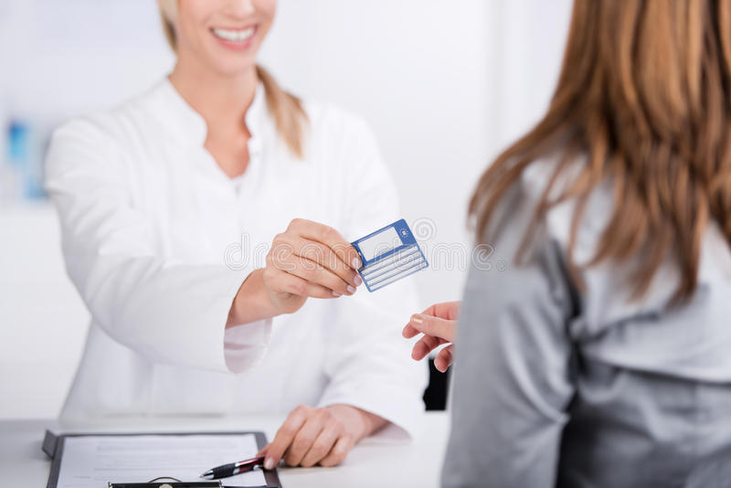 Health card. Smiling young doctor giving health card to a patient stock image