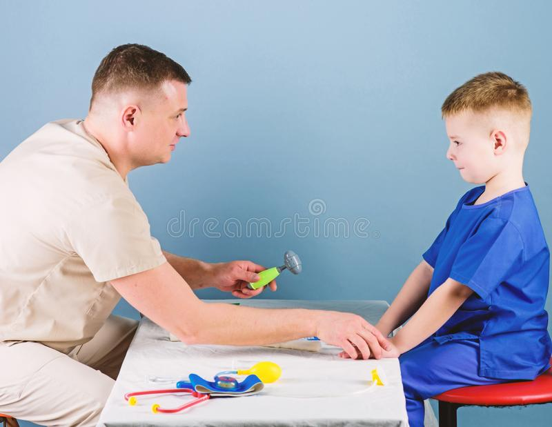 Health care. Child care. Careful pediatrician check health of kid. Medical examination. Medical service. Man doctor sit. Table medical tools examining little royalty free stock photos