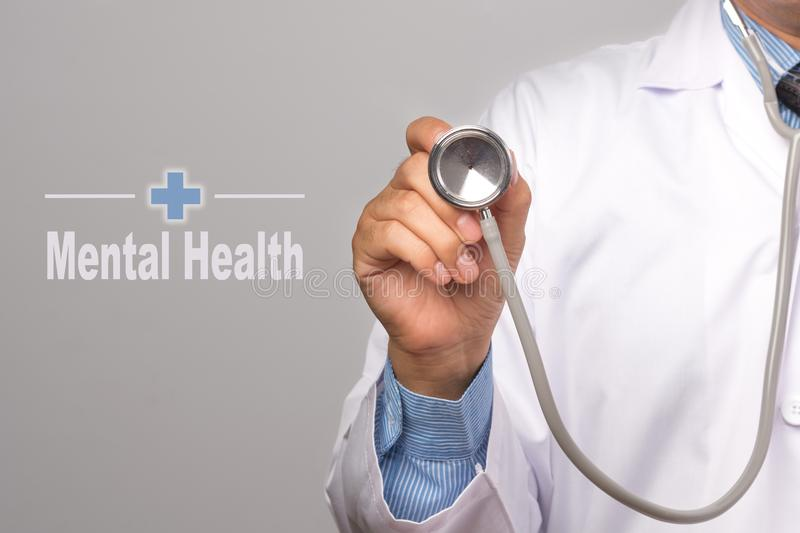 Health Care Concept. Doctor holding a stethoscope and Mental Health word on gray background. royalty free stock photography