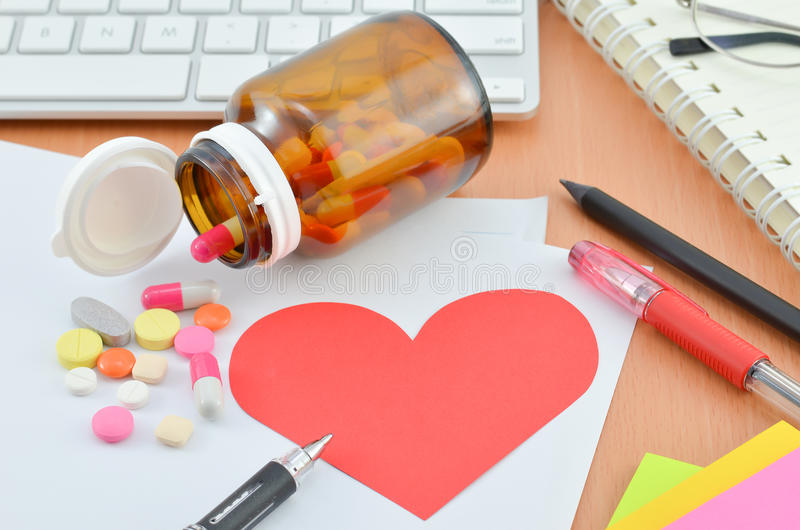 Health Care Concept - Red heart with supplement on computer desk. Health Care Concept - Red heart note paper with supplement on computer desk royalty free stock images