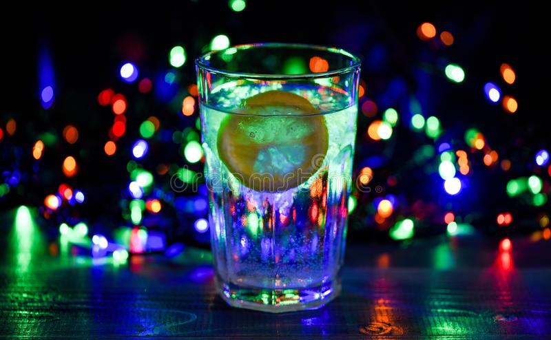 Health care concept. What to drink on christmas party. Cocktail glass with water and slice of lemon defocused garland stock images
