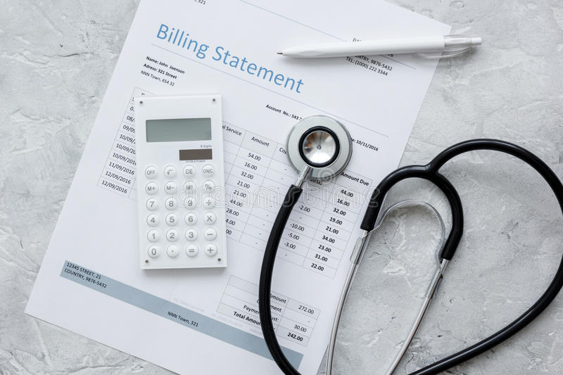 Health care costs with billing statement, stethoscope and calculator on stone table top view royalty free stock images