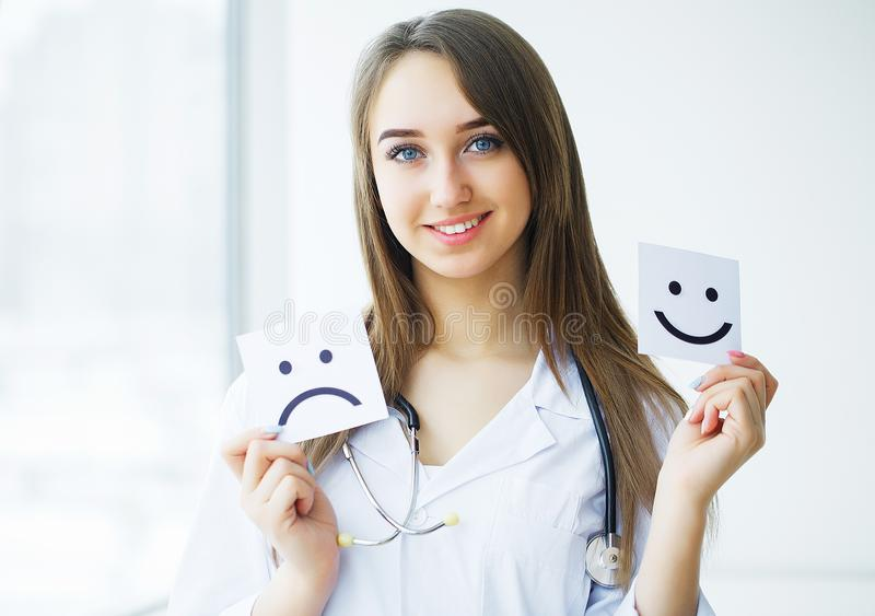 Health Care. Doctor Holding a Cards With Symbol Fun and Sad Smile, Medical Concept stock photo