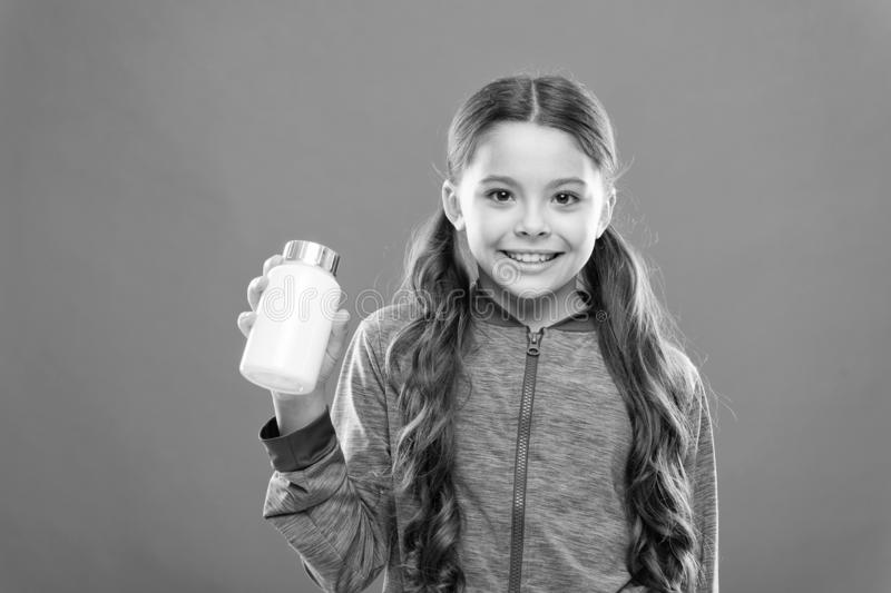 Health care. Girl long hair hold medicines bottle. Vitamin concept. Need vitamin supplements. Child cute girl take some stock photo