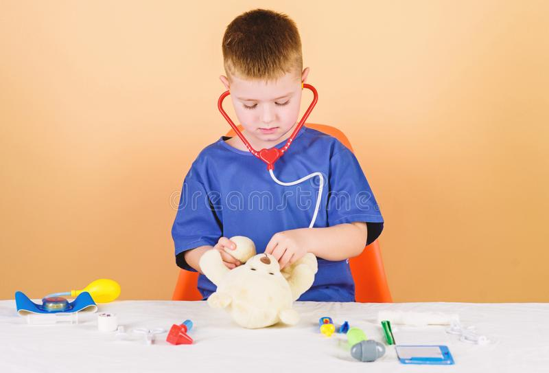 Health care. Kid little doctor busy sit table with medical tools. Medical examination. Medicine concept. Medical. Procedures for teddy bear. Medical education stock image