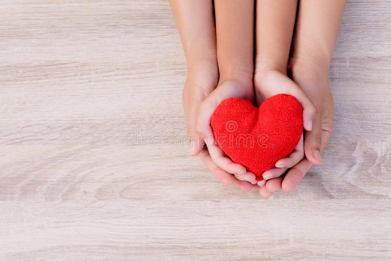Health care, love, organ donation, family insurance and CSR concept. Adult and child hands holding handmade red heart on wooden background royalty free stock photo