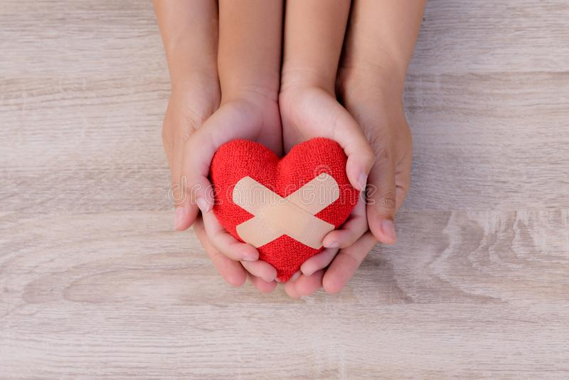 Health care, love, organ donation, family insurance. And CSR concept. adult and child hands holding handmade red heart on wooden background. First Aid Band stock photos