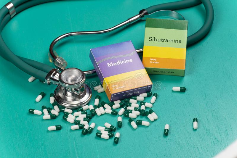 Health care medical and sickness concept. Pills and medical equipment background with a drug box fake write & x22;Medicine. Stethoscope white capsule view top royalty free stock photo