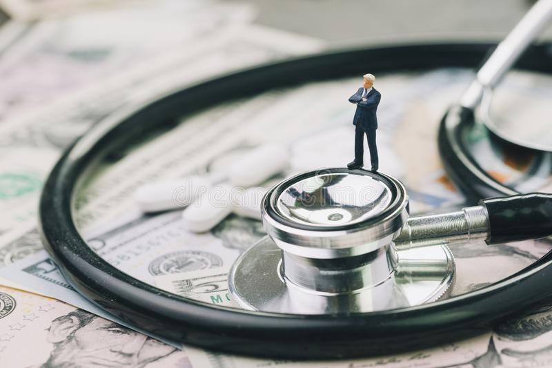Health care, pharmaceutical and medical industry business concept, miniature businessman standing on stethoscope and white tablet stock photos