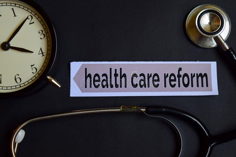 Health care reform on the print paper with Healthcare Concept Inspiration. alarm clock, Black stethoscope. stock photography