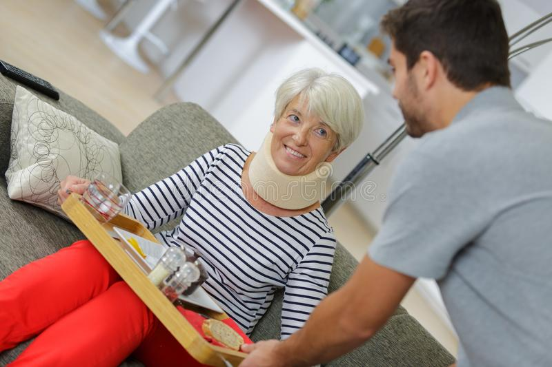 Health care worker helping elderly woman stock photos