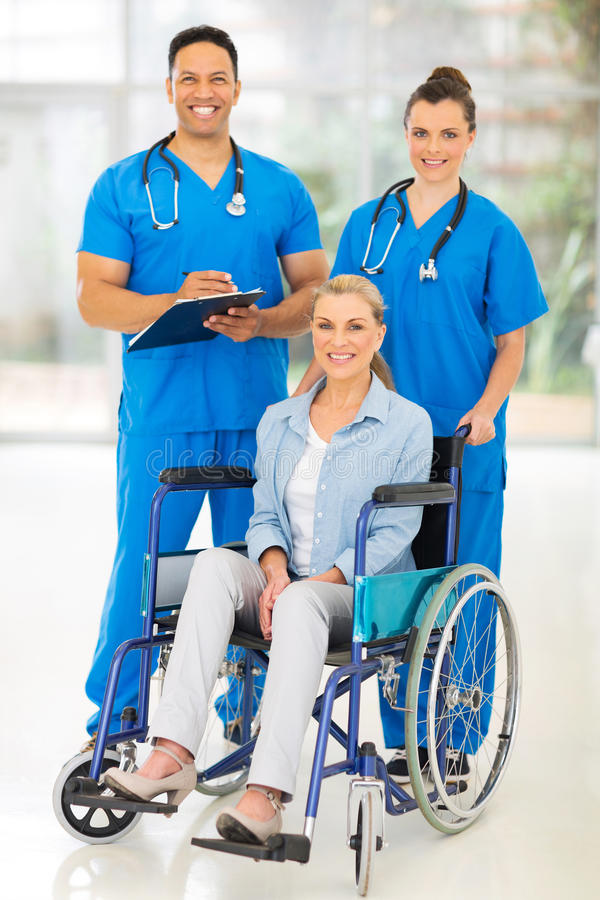 Health care workers patient. Two professional health care workers and disabled patient stock photo