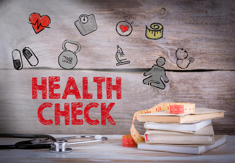 Health Check. Stack of books and a stethoscope on a wooden background.  royalty free stock photos