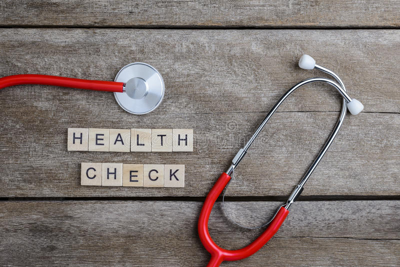 Health Check text word made with wood blocks and Red Heart,stethoscope on wooden table. Health background concepts stock images