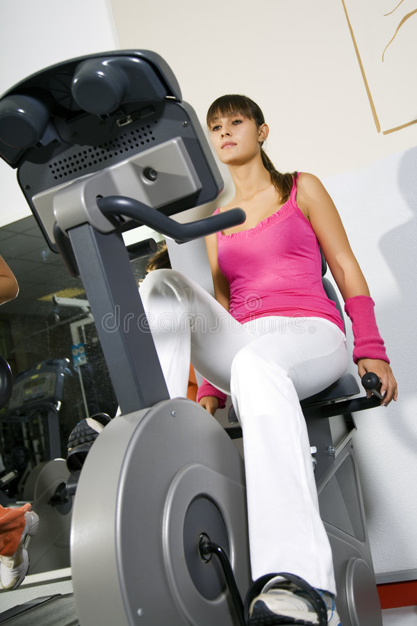 Health club. Young girl working out on a cyclette royalty free stock images
