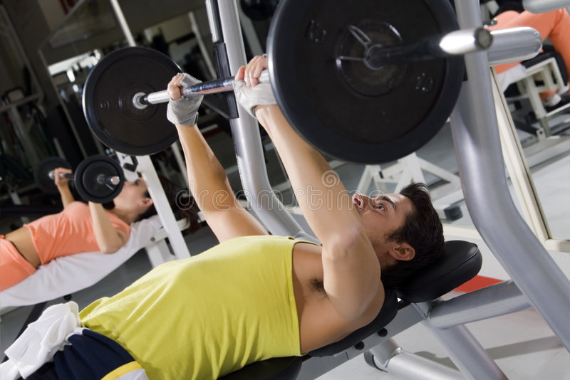 Health club. Guy in a gym doing weight lifting royalty free stock images