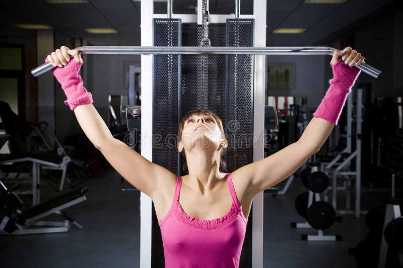 Health club. Girl in a gym doing weight lifting royalty free stock images