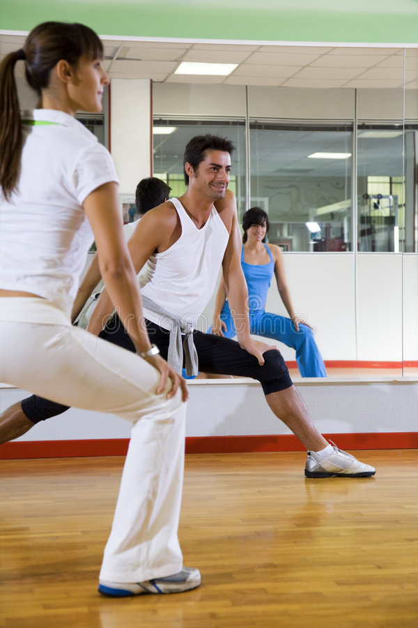 Health club. Man and women doing stretching and aerobics royalty free stock images