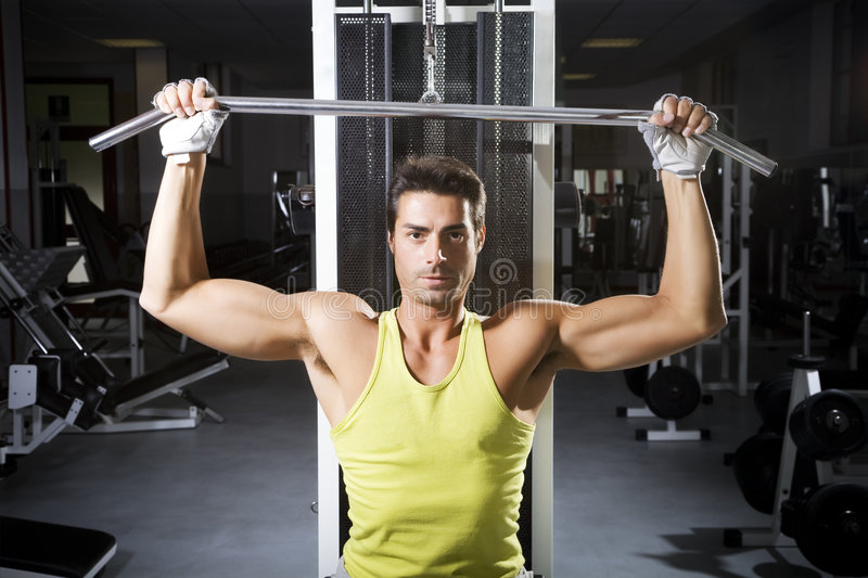 Health club. Man in a gym doing weight lifting royalty free stock photography
