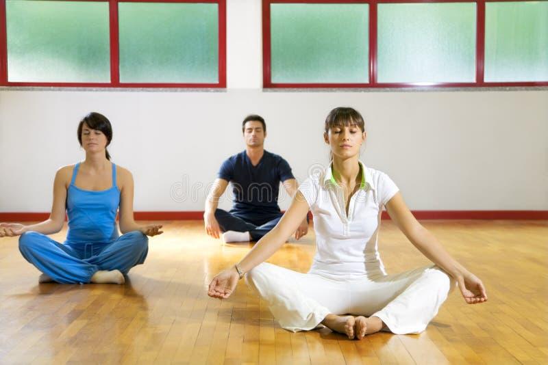 Health club. Man and women doing yoga royalty free stock photos