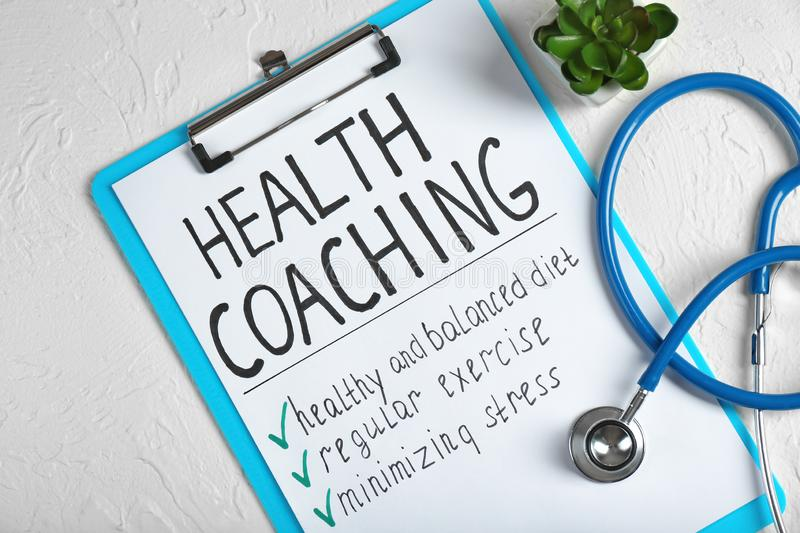 Health coaching written on sheet of paper with stethoscope on white textured background royalty free stock images