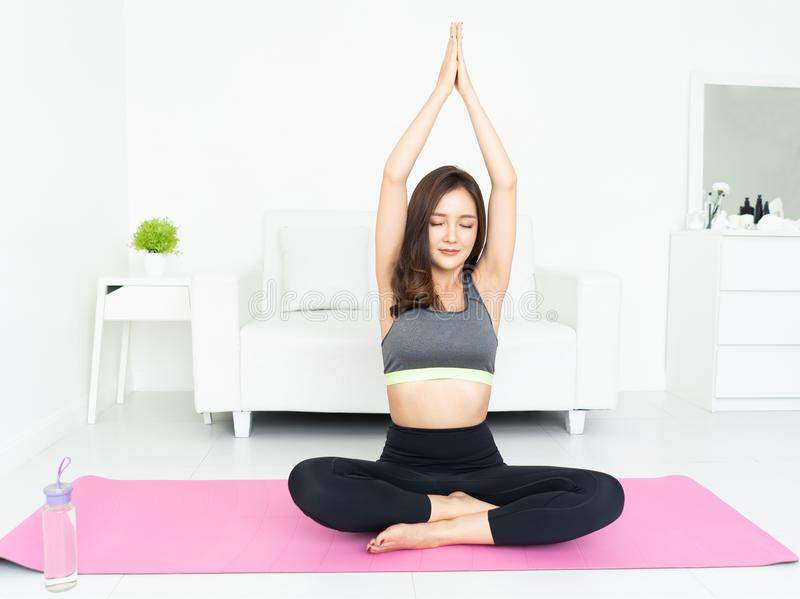 Health concept. Attractive young Asian woman sitting on mat  practicing yoga with eyes closed at her home. stock photos