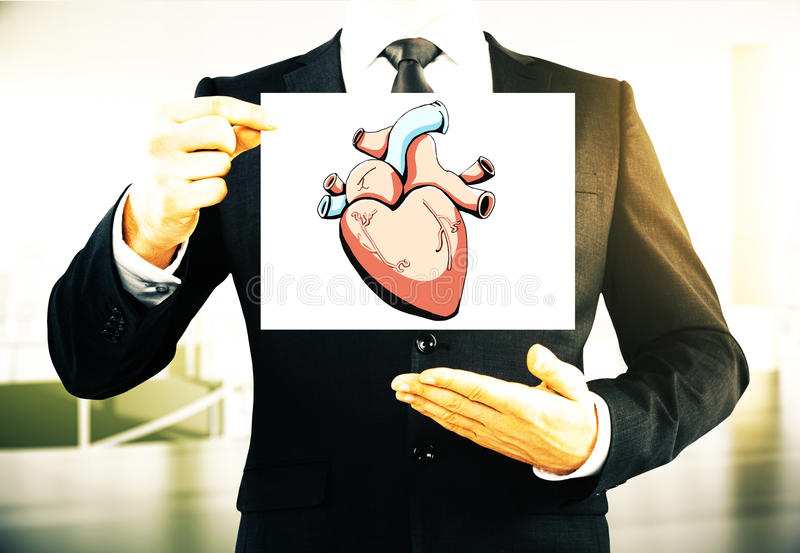 Health concept. Businessman holding card with creative realistic heart sketch on blurry background. Health concept royalty free stock photography