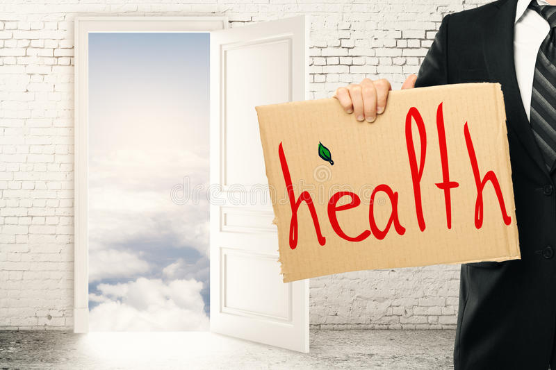Health concept. Businessman holding cardboard poster with health text in abstract interior with brick wall and door leading to heaven. 3D Rendering royalty free stock photos