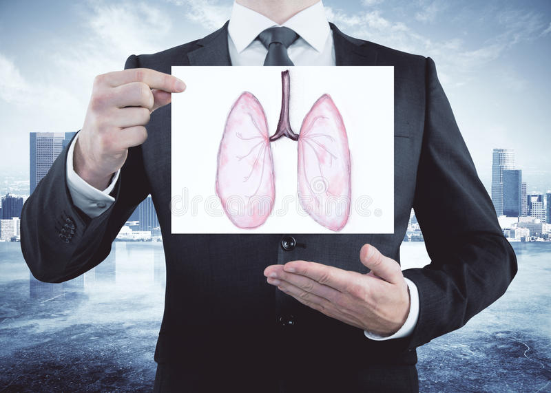 Health concept. Businessman holding and showing card with healthy lungs sketch on city background. Health concept stock photos