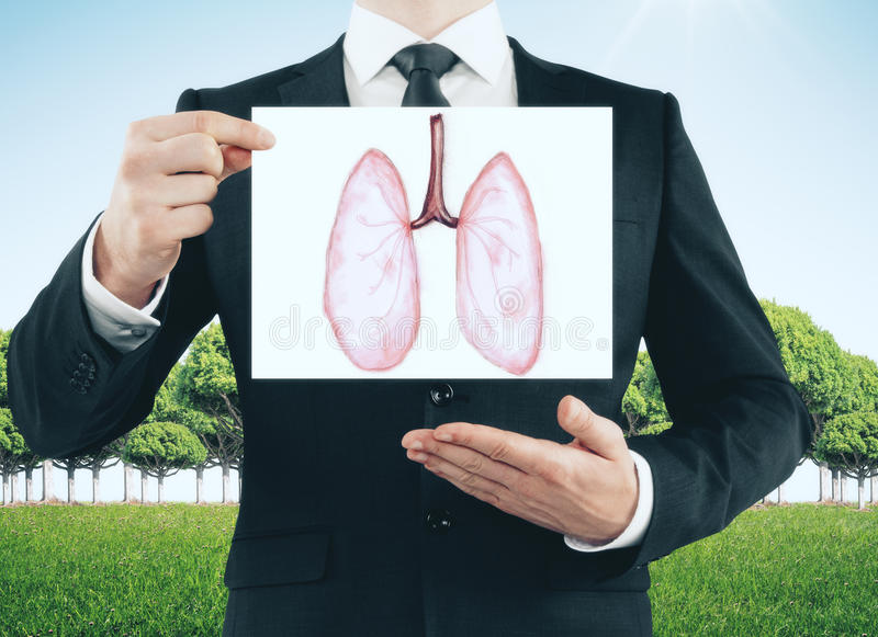 Health concept. Businessman holding and showing card with healthy lungs sketch on landscape background. Health concept stock image