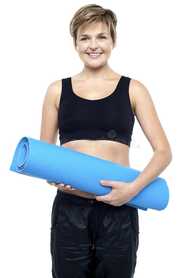 Health Conscious Woman Holding Blue Exercise Mat Royalty Free Stock Photos